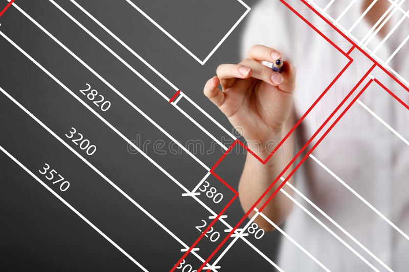 Focused caucasian female architect working at drawing touch board at office. Floor plan, busy, concentration concept royalty free stock image