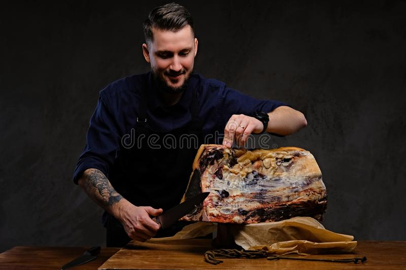 Focused chef cook cutting exclusive jerky meat on a table in a hunting house on dark background. stock image