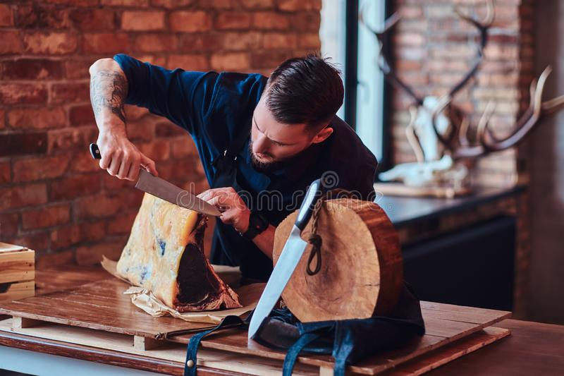 Focused chef cook cutting exclusive jerky meat on a table in kitchen with loft interior. royalty free stock photos