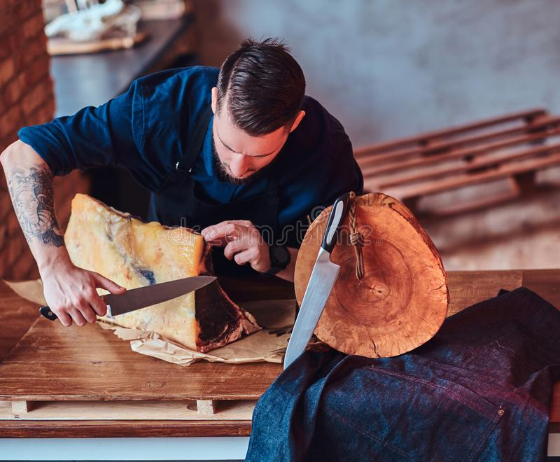 Focused chef cook cutting exclusive jerky meat on a table in kitchen with loft interior. royalty free stock photography