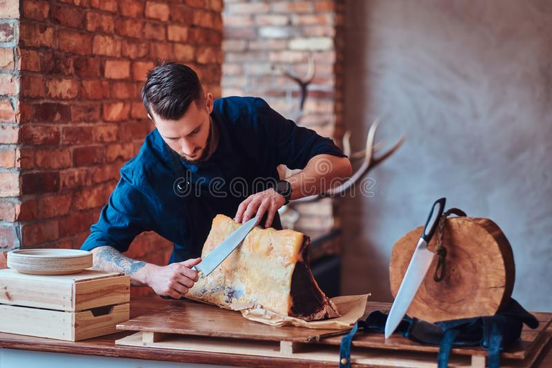 Focused chef cook cutting exclusive jerky meat on a table in kitchen with loft interior. stock images