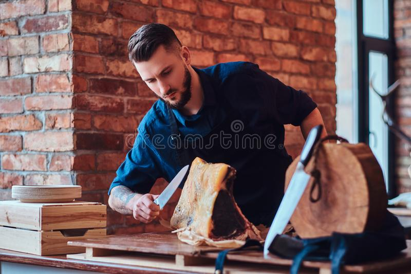 Focused chef cook cutting exclusive jerky meat on a table in kitchen with loft interior. royalty free stock photo