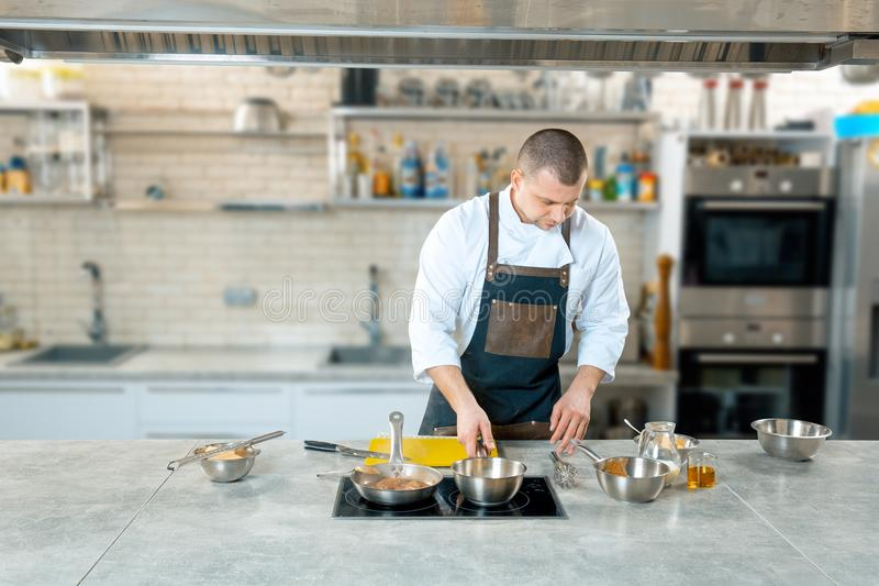 Chef preparing a polenta in the restaurant kitchen. cooking process royalty free stock photos