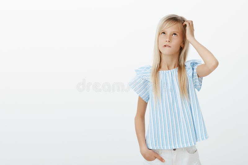 Focused clueless girl trying to calculate in mind near blackboard. Portrait of confused questioned kid in stylish blue royalty free stock photos