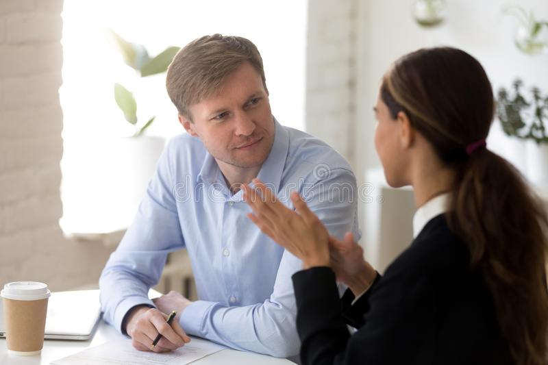 Middle aged male recruiter listening to young female job applicant. stock images