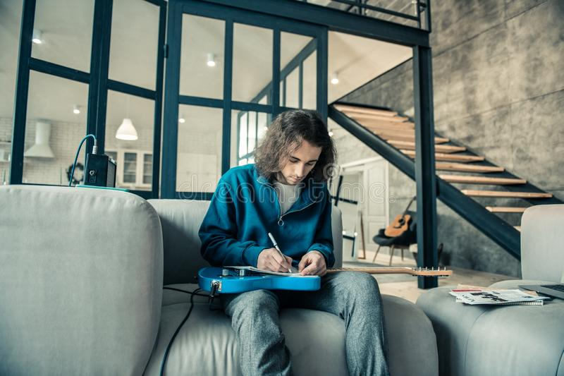 Focused dark-haired guy writing down notes in special album royalty free stock photography