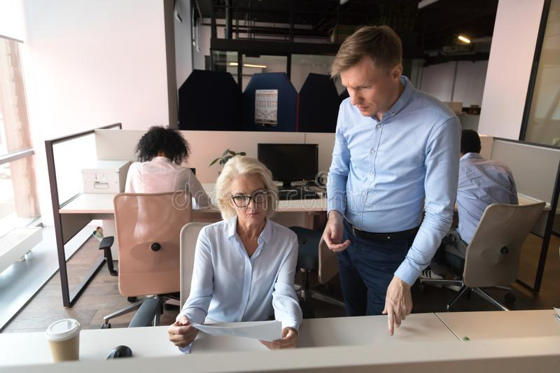 Focused diverse colleagues discuss paperwork in coworking space. Senior female employee show document discuss report with male colleague in coworking office stock images