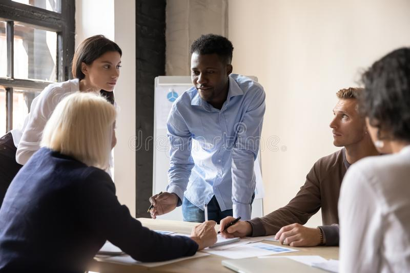 Focused diverse coworkers developing marketing strategy at office. Concentrated african american young manager answering questions of middle aged confident team stock image
