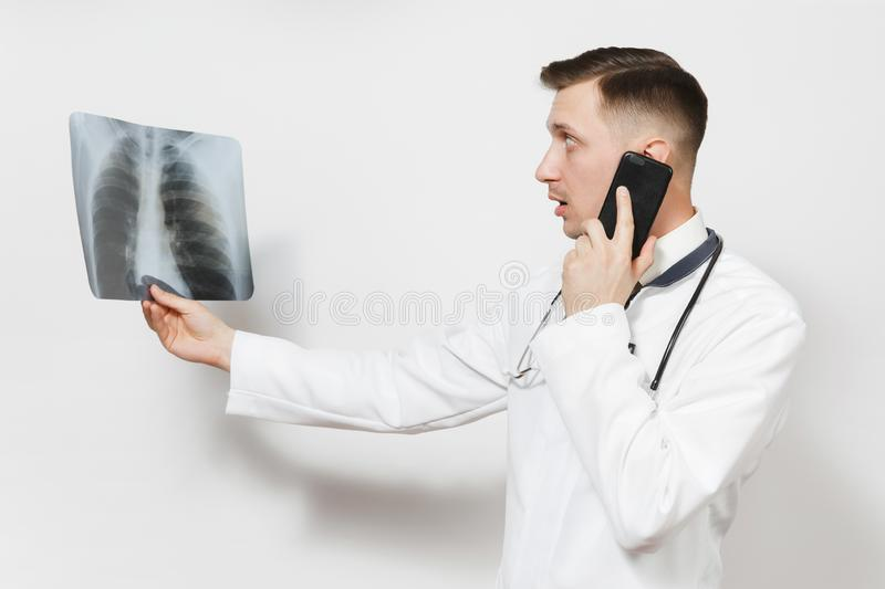 Focused doctor man with X-ray of lungs, fluorography, roentgen, talking on mobile phone isolated on white background. Male doctor in medical uniform stock photo