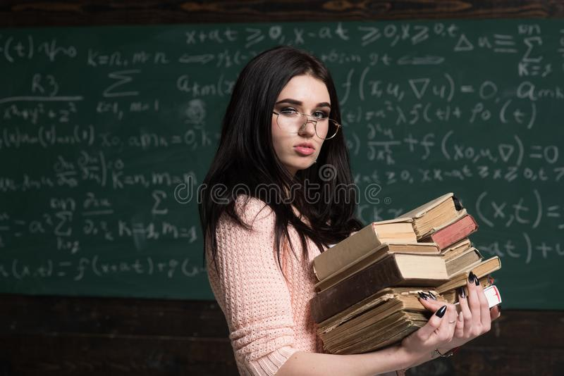 Focused on exam. Girl student preparing for examination. Student excellent fond of studying. Diligent student preparing. For exam test. Girl holds heavy pile of stock photos