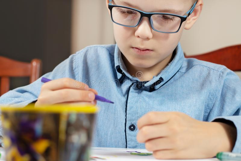 Focused face of a boy in a blue shirt and glasses while painting the picture. The boy is holding a felt-tip pen in his hand. Focused face of a boy in a blue royalty free stock photography
