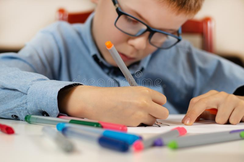 Focused face of a boy in a blue shirt and glasses while painting the picture. The boy is holding a felt-tip pen in his hand. The boy in a blue shirt and stock photography