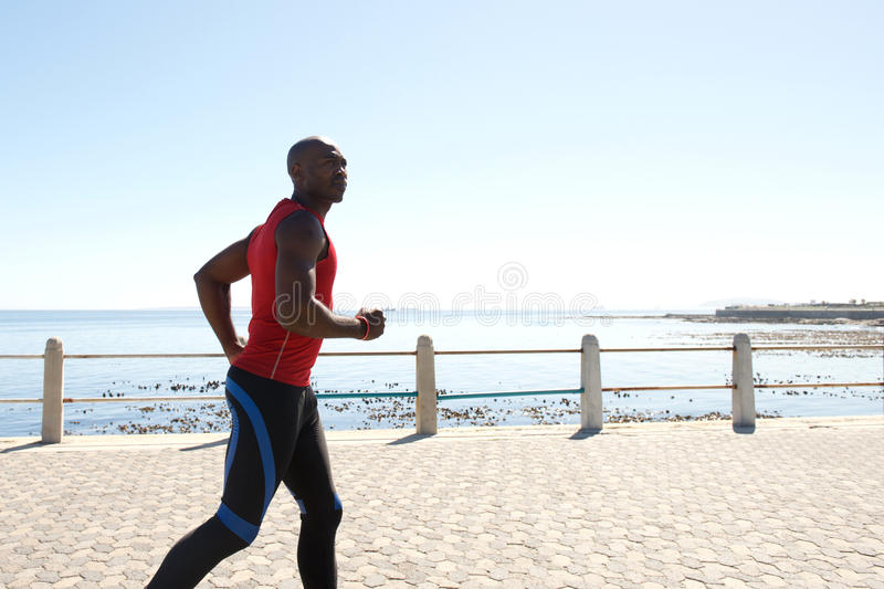 Focused fit african man jogging at promenade royalty free stock photography