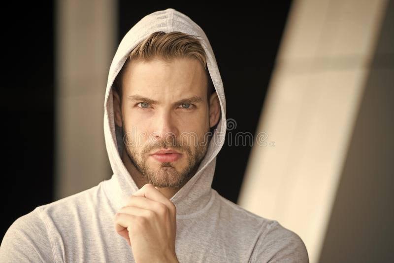 Focused future achievement. Guy bearded attractive casual clothes hooded. Man with bristle concentrated face urban. Background defocused. Man unshaven guy looks stock images
