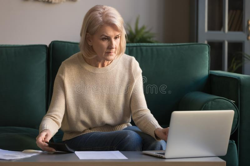 Focused grey haired mature woman calculating bills, using laptop. Online bank service, checking domestic finances, serious middle aged female looking at royalty free stock photography