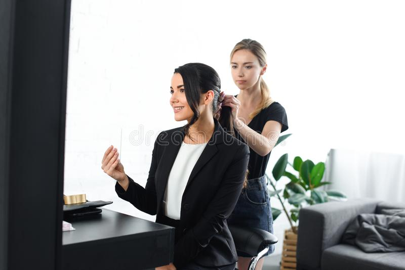 focused hairstylist doing hairstyle while smiling businesswoman stock photo