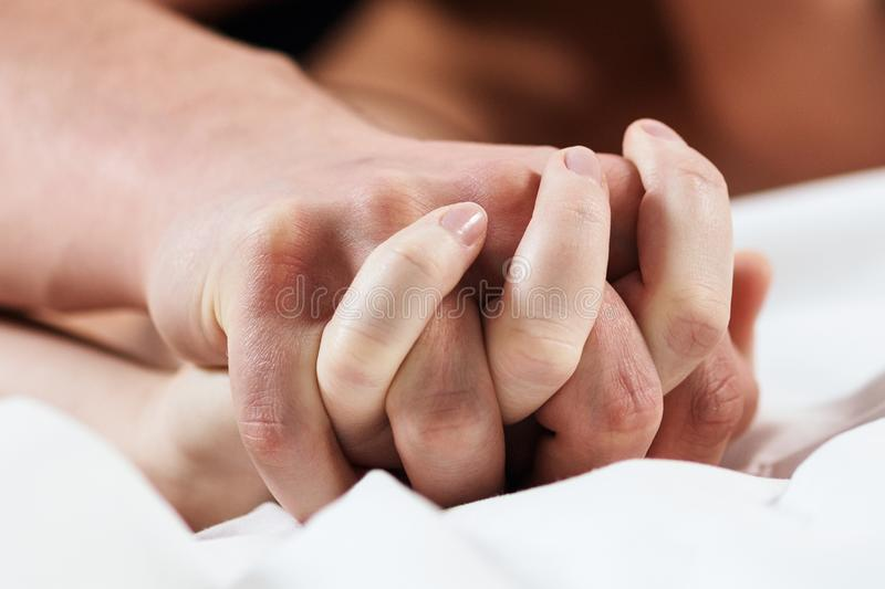 Focused on hands of passion couple having sex. stock images