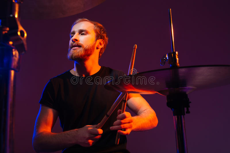 Focused handsme bearded drummer playing drums stock photo