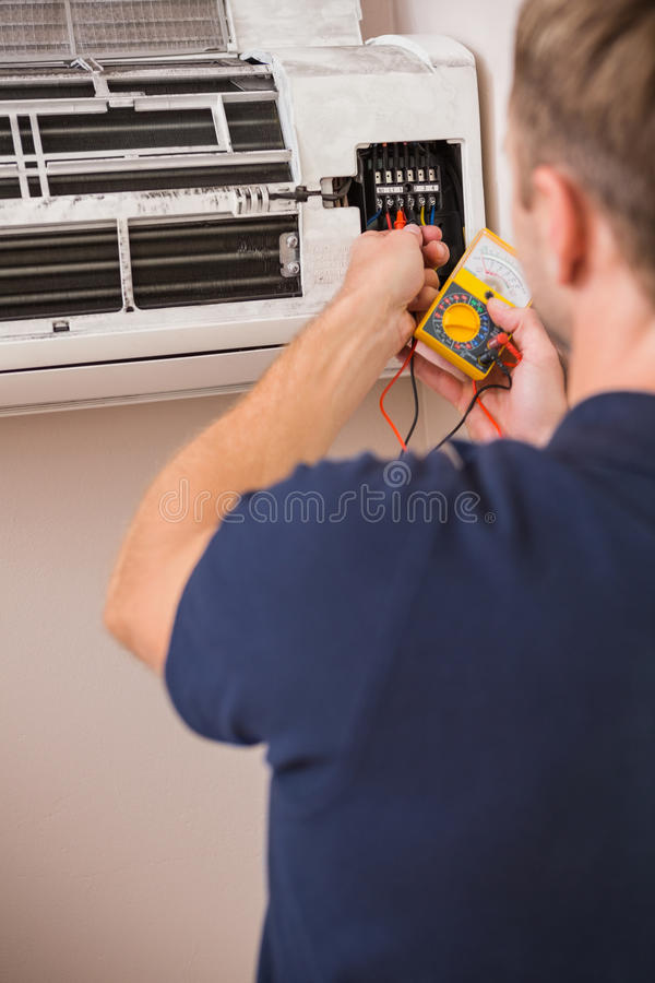 Focused handyman testing air conditioning stock image