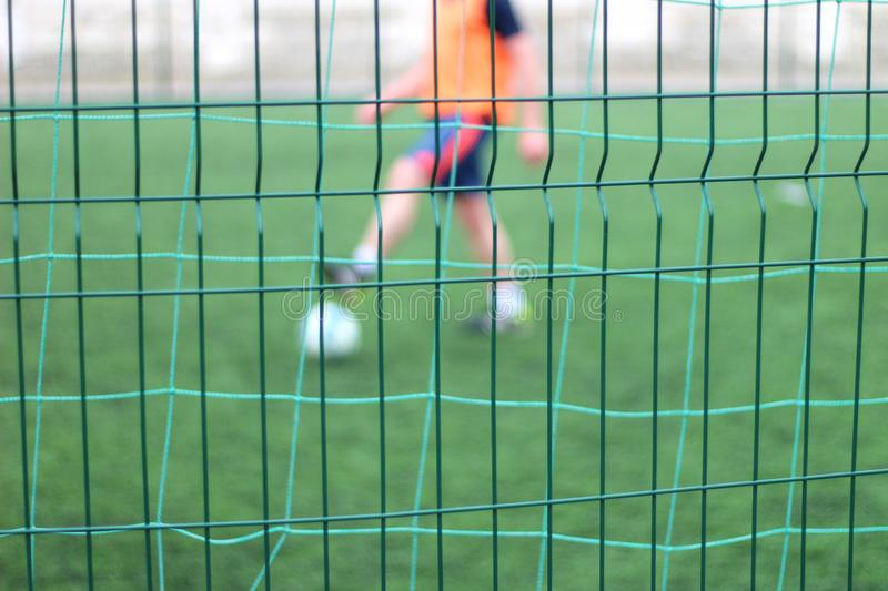 Focused image of sectional green fence. Soccer players with a ball plays on the background. Football, field, port, outdoor, game, pitch, activity, young, goal stock photo