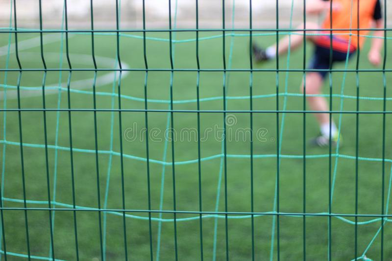 Focused image of sectional green fence. Soccer players with a ball plays on the background. Football, field, port, outdoor, game, pitch, activity, young, goal royalty free stock photo