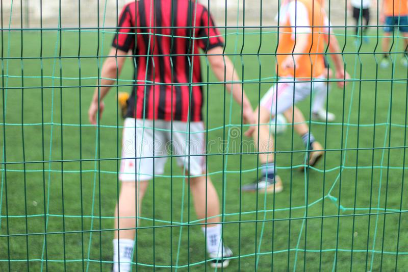 Focused image of sectional green fence. Soccer players with a ball plays on the background. Football, field, port, outdoor, game, pitch, activity, young, goal stock images