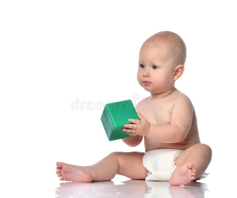 Quiet infant child baby boy in diaper is sitting on the floor with a green cube, playing, giving, taking on white. Focused infant child baby boy toddler in royalty free stock photo