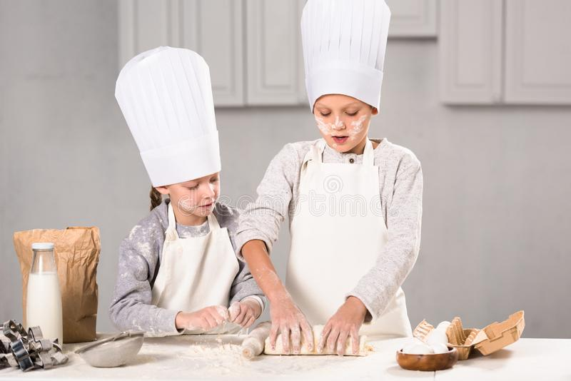 Focused kids in aprons and chef hats making dough with rolling pin at table. In kitchen stock images