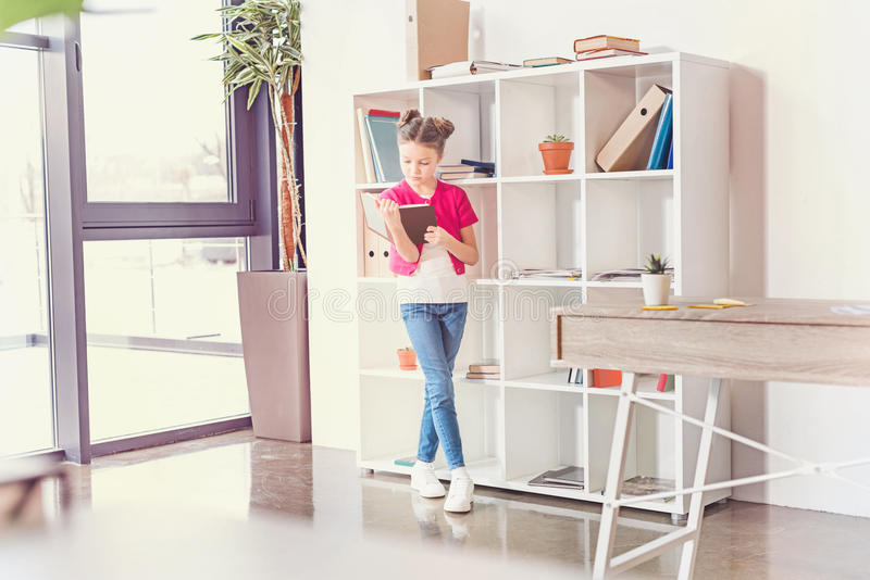 Focused little girl standing and reading book in office royalty free stock images