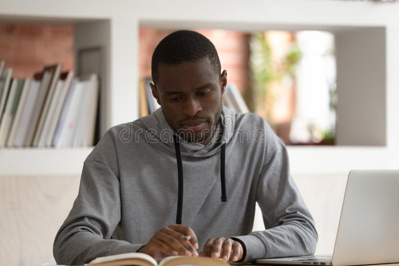 Focused male african american student preparing for final examination. royalty free stock images