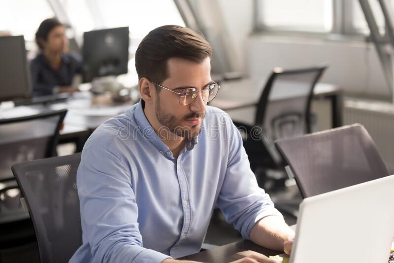Focused male employee busy working on laptop stock photos