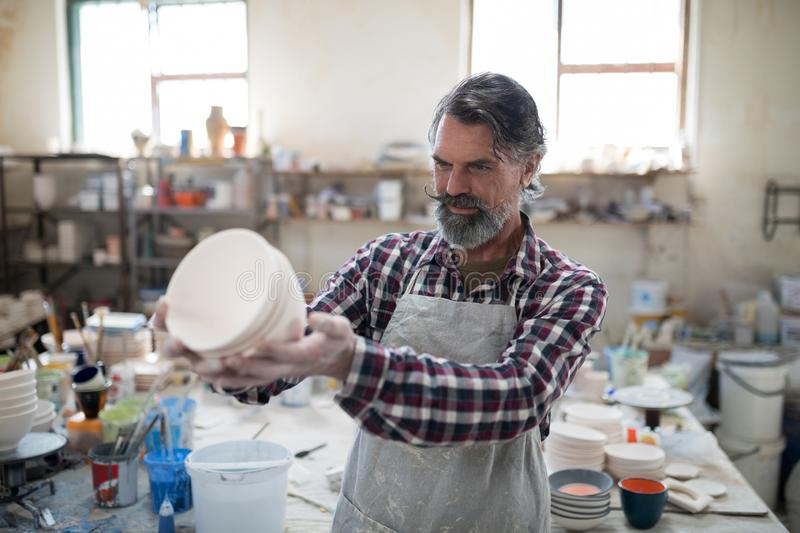 Focused male potter examining his creation for flaws. In the pottery workshop stock images