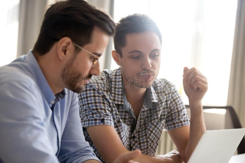 Focused male colleagues brainstorm in office working on laptop royalty free stock photo