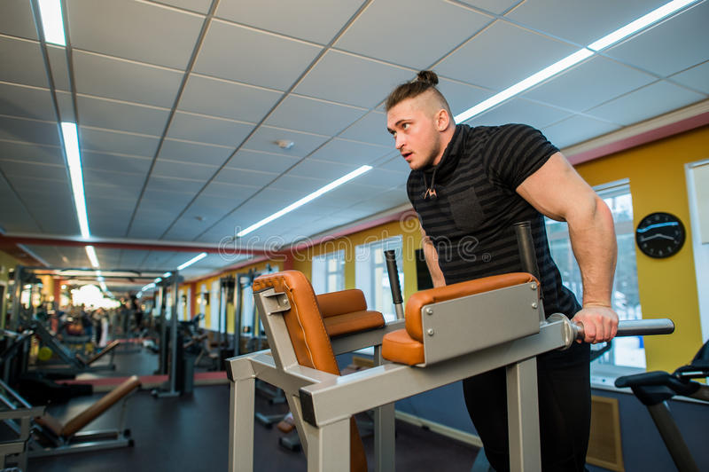 Focused man doing dips in the gym stock photo