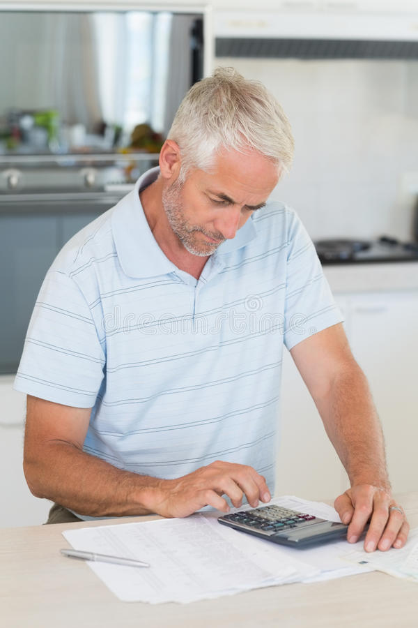 Focused man figuring out his finances. At home in the kitchen royalty free stock image