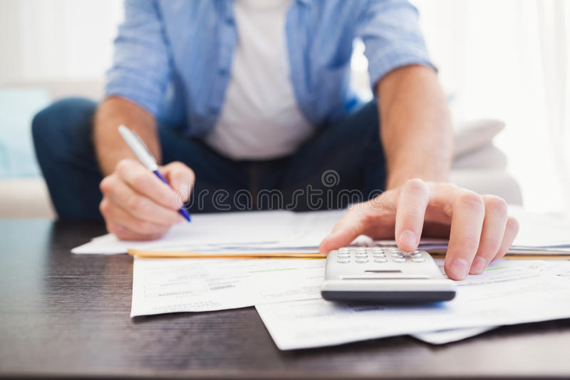 Focused man figuring out his finances. In the living room royalty free stock photos