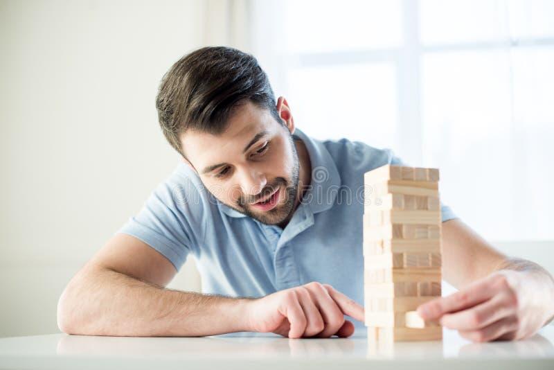 Focused man playing jenga game at home royalty free stock photo