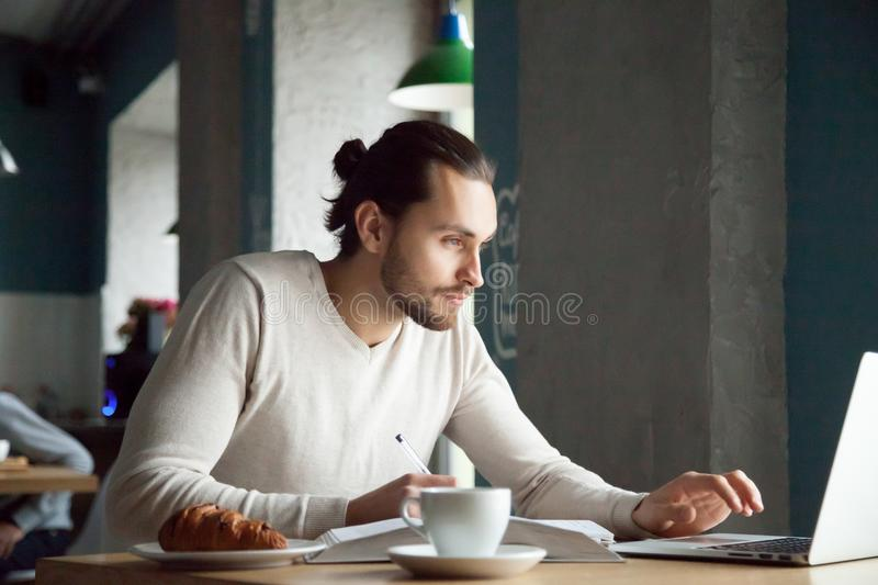 Focused man writing notes learning online with laptop in cafe stock image