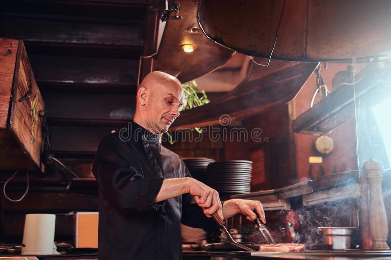 Focused master chef wearing uniform cooking delicious beef steak on a kitchen in a restaurant. royalty free stock photos