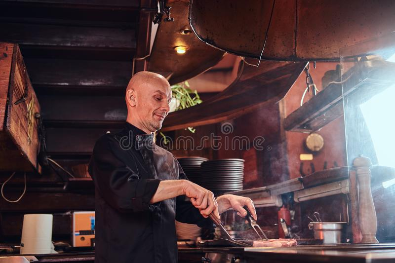 Focused master chef wearing uniform cooking delicious beef steak on a kitchen in a restaurant. royalty free stock image