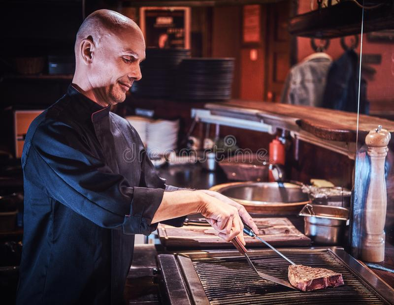 Focused master chef wearing uniform cooking delicious beef steak on a kitchen in a restaurant. royalty free stock photo