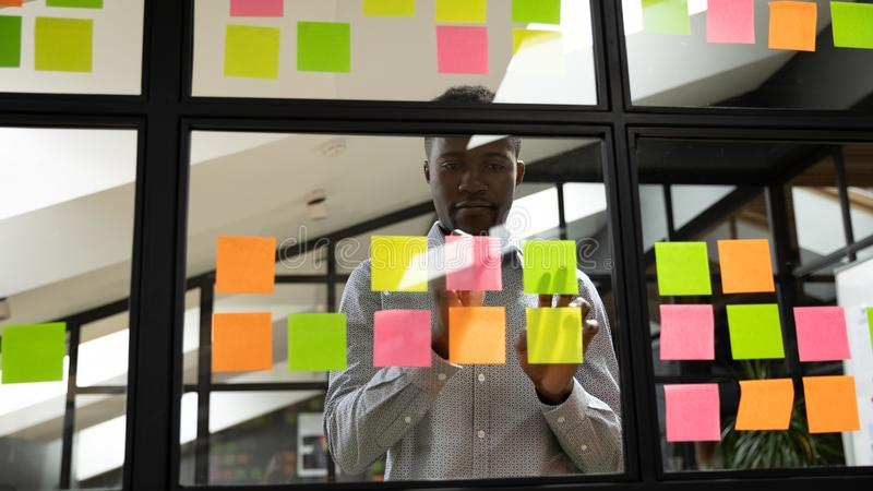 Focused millennial african american male manager organizing working process. stock photography