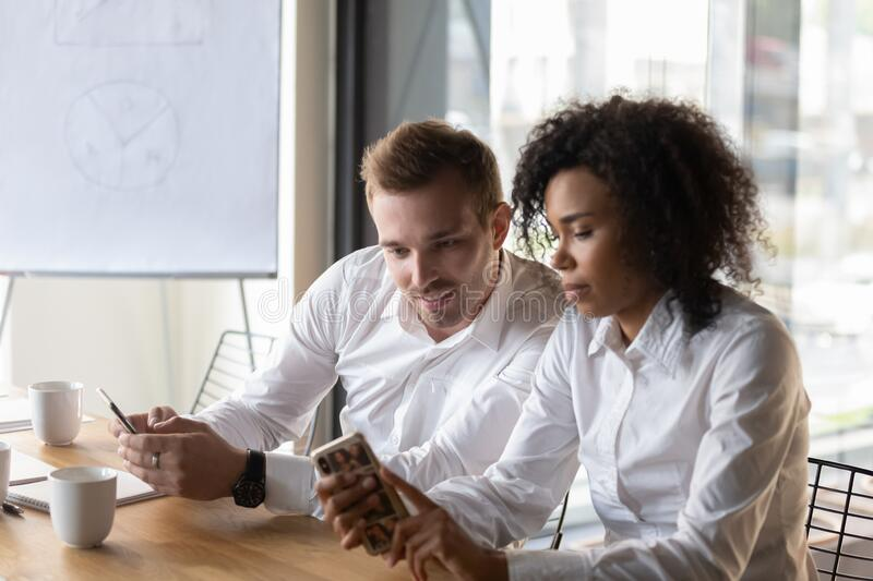 Multi-ethnic coworkers busy with smartphone new e-business application royalty free stock photo