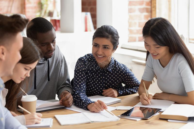 Focused multi national students sitting at desk studying together royalty free stock photo