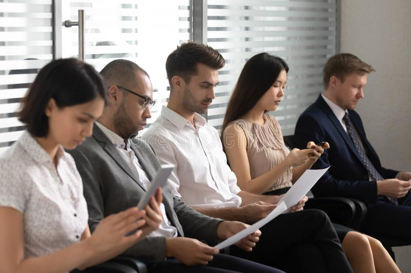 Business people applicants prepare for job interview sit in row stock image