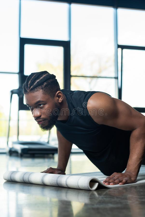 Focused muscular african american man. Doing push ups in gym stock image
