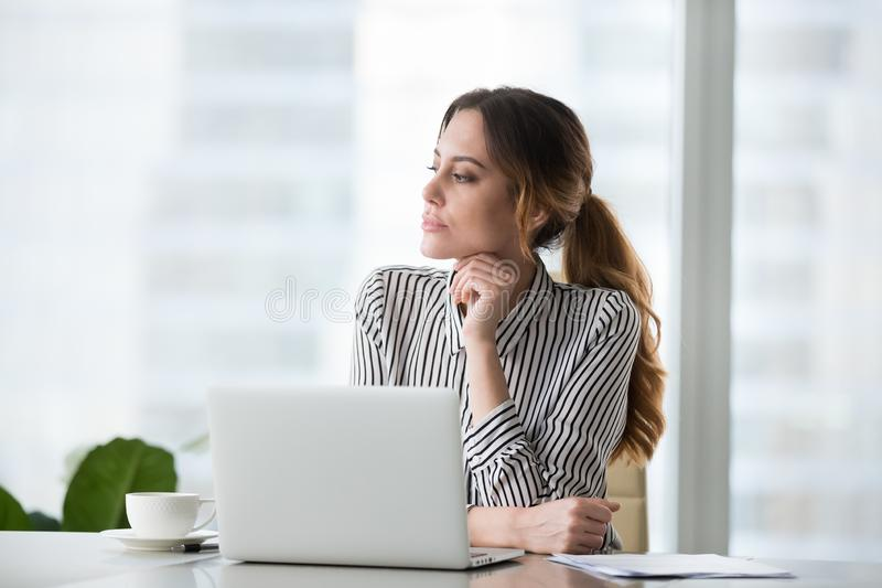 Focused pensive young woman looking in distance. stock photo