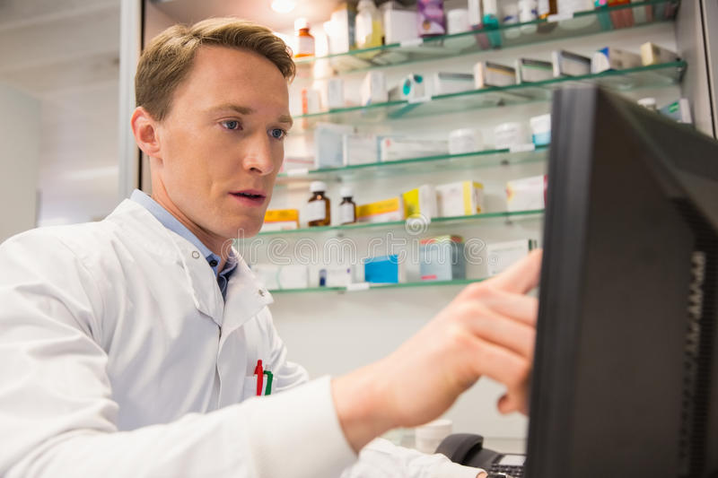 Focused pharmacist using the computer royalty free stock image