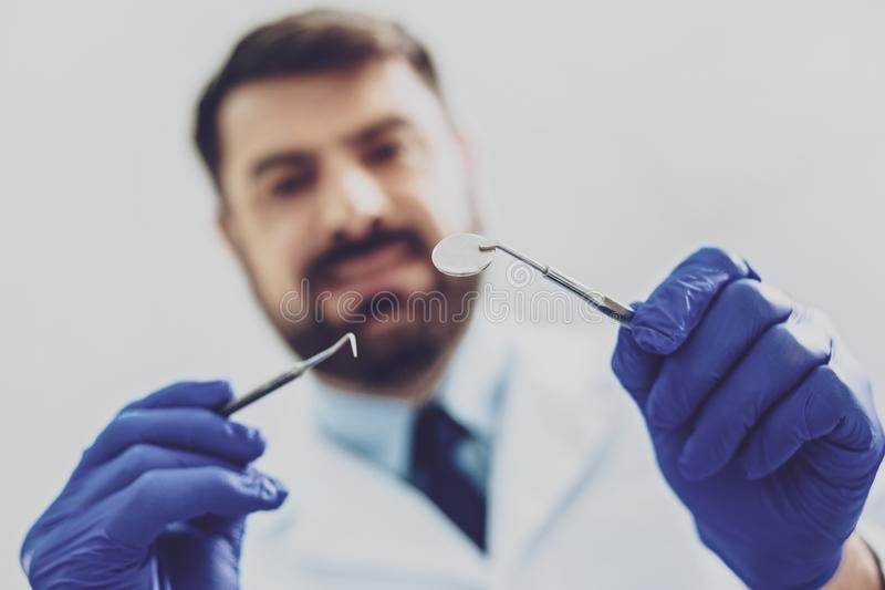 Focused photo on male hands that holding medical instrument. Sterile tools. Close up of stomatologist that expressing positivity while treating his patient royalty free stock images