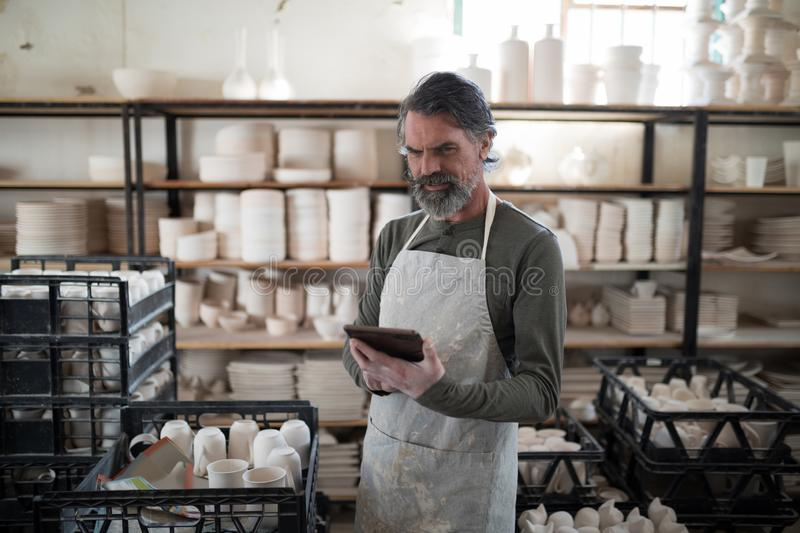 Focused potter using tablet surrounded by work. In the pottery workshop royalty free stock images